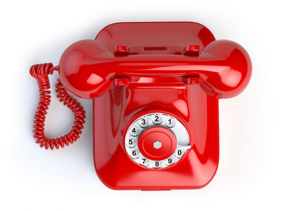 Red vintage telephone isolated on white. Top view of phone